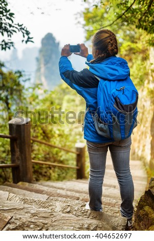 Young female tourist with blue backpack standing on stone stairs among green foliage and taking photo of beautiful mountain view. The Zhangjiajie National Forest Park, Hunan Province, China.