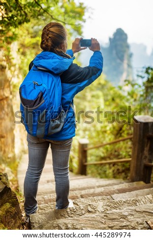 Young female tourist with blue backpack standing on stone stairs among green foliage and taking photo of beautiful mountain view in the Zhangjiajie National Forest Park, Hunan Province, China.