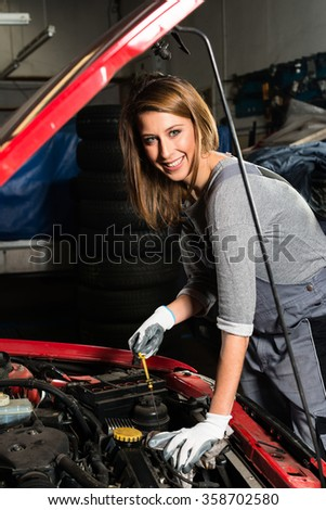 Young female trainee fixing car engine in garage - stock photo