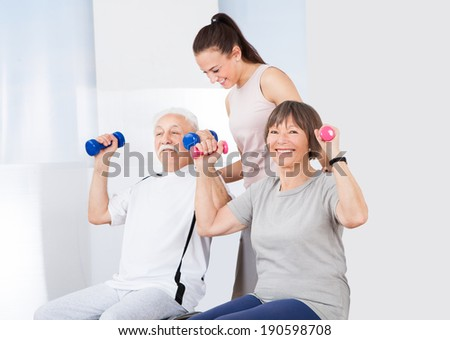 Young female trainer assisting senior couple with dumbbells at healthclub - stock photo