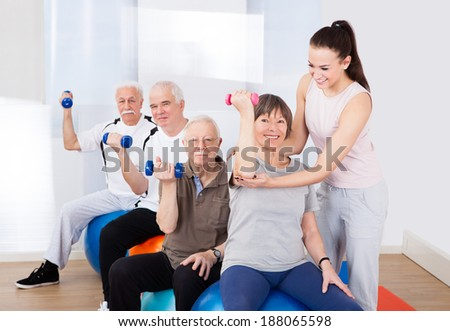 Young female trainer assisting senior people with dumbbells sitting on fitness balls at healthclub - stock photo