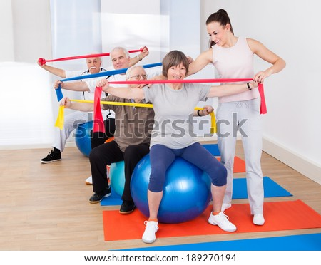 Young female trainer assisting senior people with resistance bands sitting on fitness balls at gym - stock photo