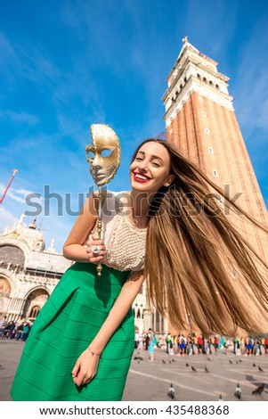 Young female traveler having fun with carnaval mask standing on San Marco square in Venice. - stock photo
