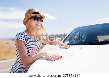 Young female traveler in hat standing near the car with tourist map - stock photo