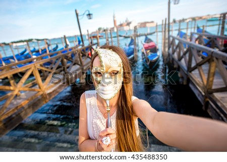 Young female traveler making selfie photo with carnaval mask standing near San Marco square with gondolas on the background in Venice. - stock photo