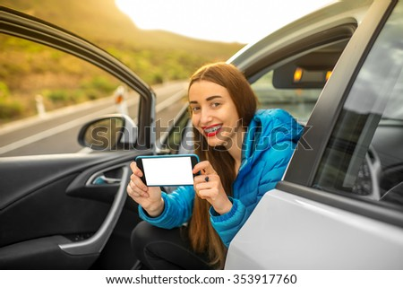 Young female traveler showing smartphone with white screen to copy space sitting in the car on the mountain road