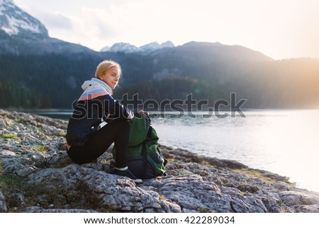 Young female traveler taking a break and enjoying the view while hiking  - stock photo