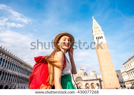 Young female traveler with hat and backpack standing on San Marco square with tower and basilica on the background in Venice. - stock photo