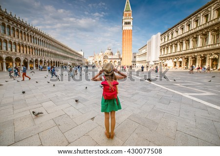 Young female traveler with hat and backpack standing on San Marco square with tower and basilica on the background in Venice. Back view with copy space - stock photo