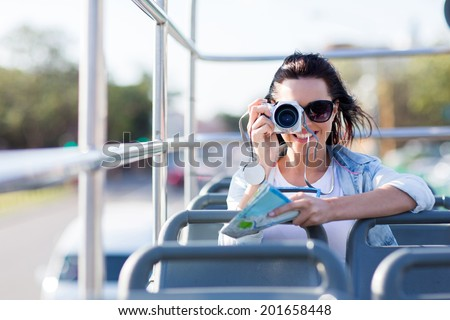 young female traveller taking photo of the city from an open top bus - stock photo