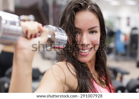 Young female using gym fitness equipment