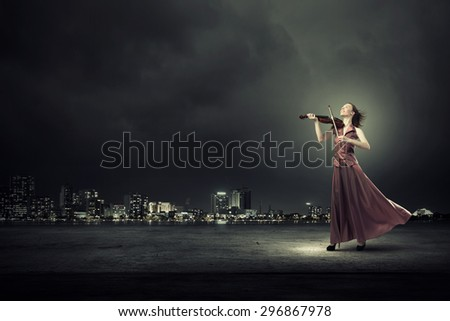 Young female violin player in long evening dress - stock photo