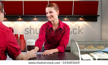 young female waitress behind the sales counter  - stock photo