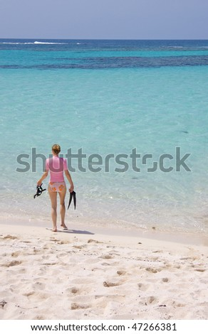 Young female walking into tropical water to go snorkeling.