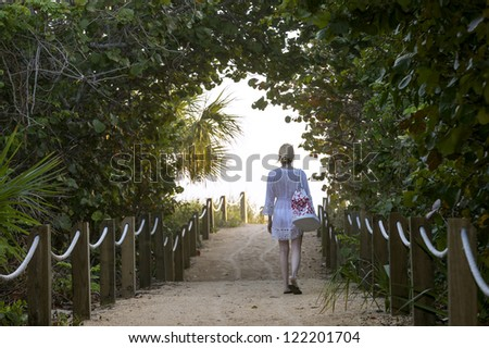 young female walking to the ocean front beach in the early morning - stock photo