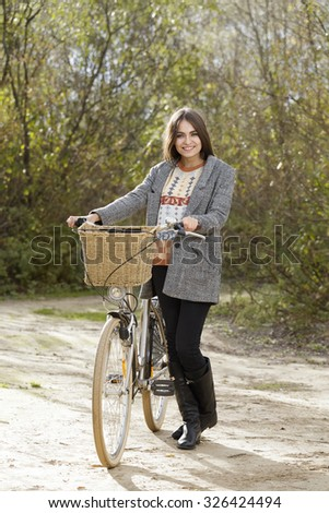 Young female walking with bicycle in a park.