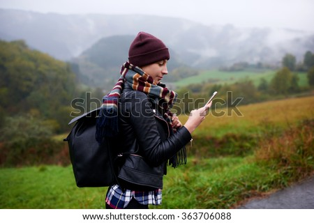 Young female wanderer search position navigation on mobile phone to find right way during adventure tour in mountains, woman hiker checks weather forecast via cell telephone while climbs the mountain - stock photo