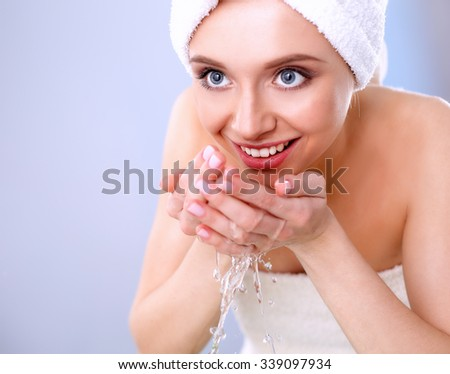 Young female washing her face with clear water
