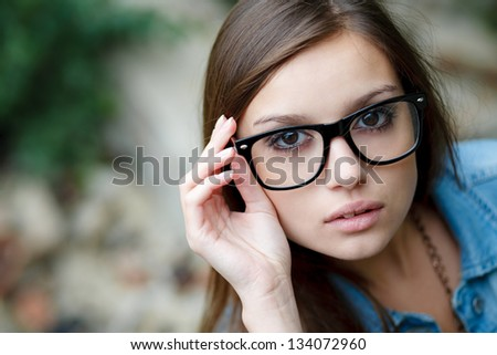 young female wear glasses holding rim with fingers looking directly in camera closeup - stock photo