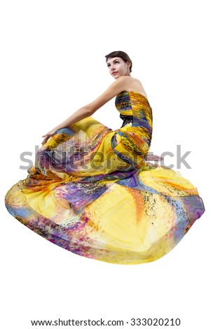 Young female wearing a fashionable yellow silk tie dye dress.  She is isolated on a white background.  The pattern is a generic tie dye with rainbow colors. - stock photo