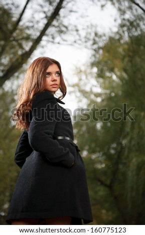 young female wearing black coat in forest looking away