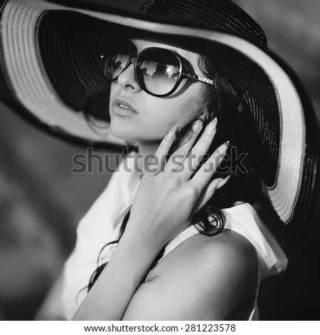 Young female wearing hat and sunglasses, posing outside.