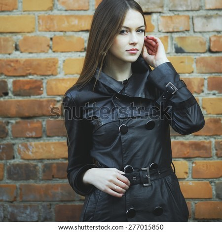Young female with beautiful long hair, wearing leather jacket, posing against brick wall.  - stock photo