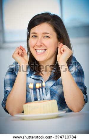 Young female with birthday cake in front of her, focus is on her face, cake is blurred - stock photo