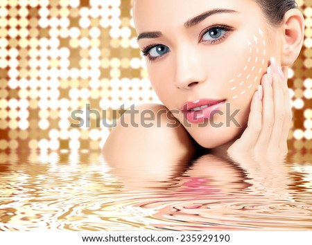 Young female with clean fresh skin, abstract background with blurred lights - stock photo