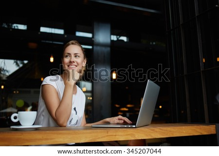 Young female with cute smile sitting with portable net-book in modern coffee shop interior during recreation time, charming happy woman student using laptop computer to prepare for the course work  - stock photo