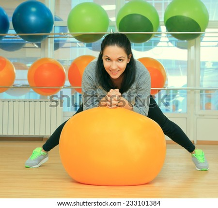 Young female with fit ball in sport center - stock photo