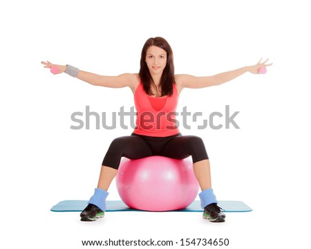 young female with fitness ball and dumbbells in sport center - stock photo