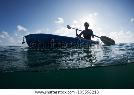 young female with sunglasses on paddling a kayak - stock photo