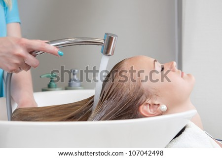 Young female woman having her hair washed and rinsed in beauty salon