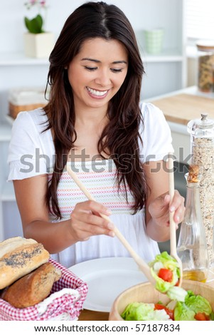 Young female woman preparing salad in kitchen at home - stock photo
