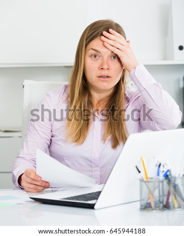 Young female worker having problem in project in office