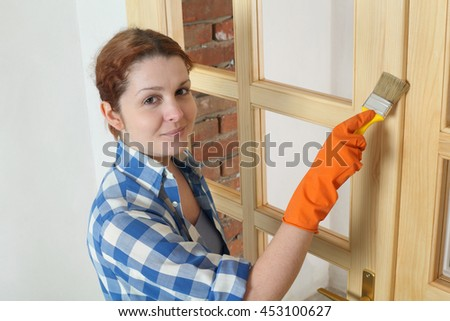 Young female worker painting new wooden door with paintbrush