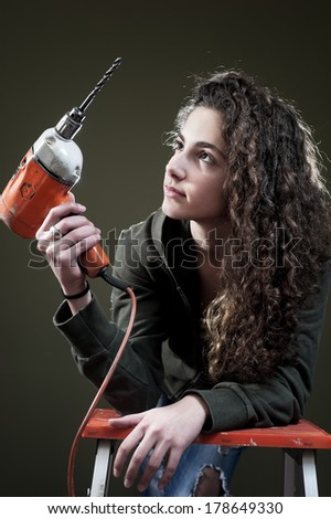 Young female working on ladder with drill