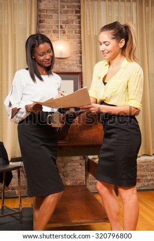 young females in the office talking over a project  - stock photo