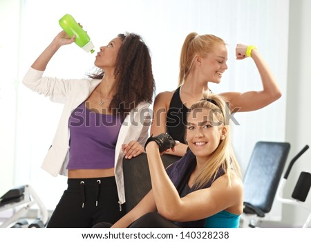 Young females showing muscles, posing, drinking water at the gym. - stock photo