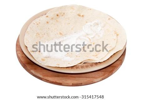 Young feta cheese spread on Mexican tortilla. - stock photo