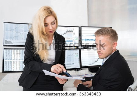 Young financial analysts discussing over documents in office