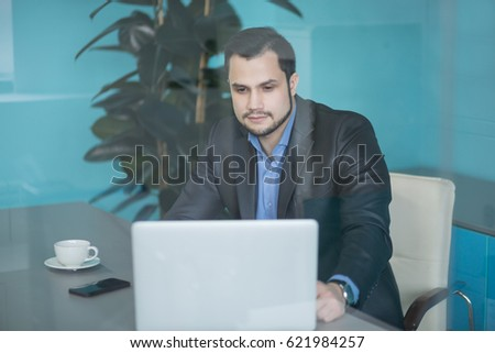Young financial businessman with laptop sitting at desk in his modern office