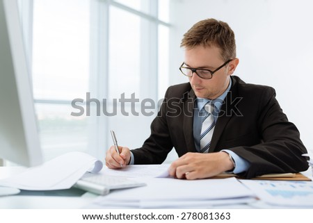 Young financial manager signing business documents