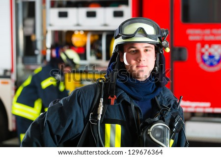 young fireman in uniform standing in front of firetruck, he is ready for deployment - stock photo