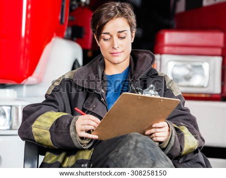 Young firewoman writing on clipboard while sitting against trucks at fire station - stock photo
