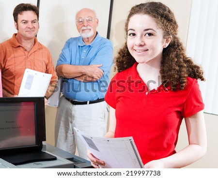 Young first time voter casting her ballot at the polls.   - stock photo