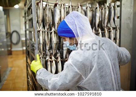 Young fish factory staff in uniform pushing cart with fresh mackerels on wires