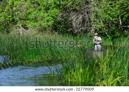 Young fisherman on the river - stock photo