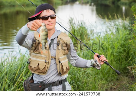 Young fisherman on the river bank. Fisherman caught a perch and holds it in his hands. . - stock photo